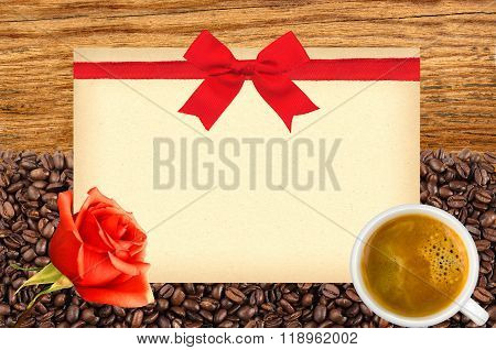 Postcard With Red Bow On Roasted Coffee Beans, White Cup And Wooden Background