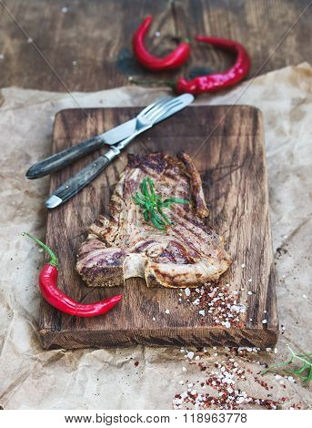 Cooked meat t-bone steak on serving board with red chili peppers, spices and fresh rosemary over oil