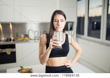 Woman in sportswear drinking banana chocolate protein powder milkshake smoothie.Drinking protein