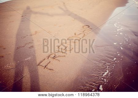 Word friendship written in the sand and two silhouettes holding hands