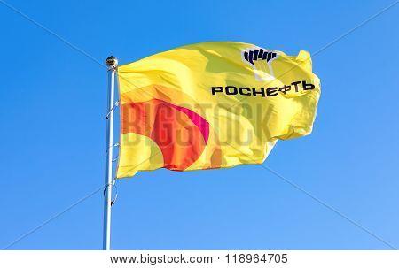 The Flag Of Oil Company Rosneft Against Blue Sky