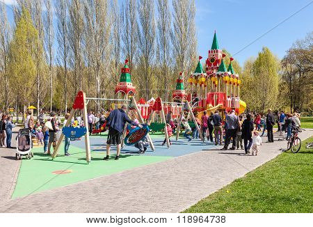 Children Play On The Playground At The Spring Park In Sunny Day