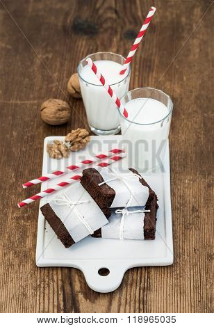 Chocolate brownie slices wrapped in paper and tired with rope, glasses of milk, stripe straws, walnu