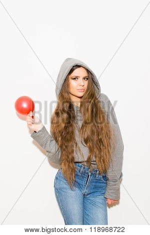 Teenage girl with long hair holding red balloon