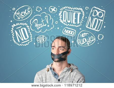 Young man with taped mouth and white drawn thought clouds around his head