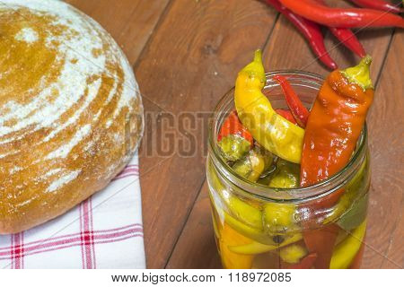 Open Pickled Chilli Peppers In Glass Jar With Bread And Fresh Chilli