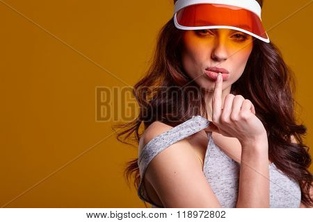 Smiling young woman in orange  sun visor posing in sunlight and looking away. studio shot on yellow background.
