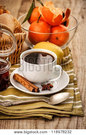 Black coffee and tangerines fruits for breakfast. Sweet jam on wooden board in rustic style