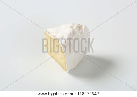 slice of white rind cheese on white background