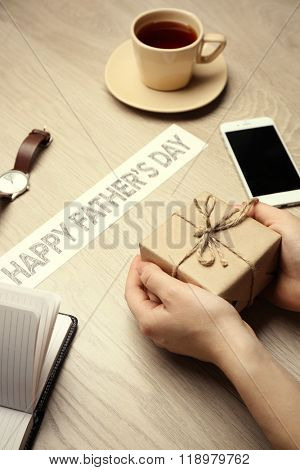 Happy Father's Day inscription with gifts and female hands on wooden background. Greetings and presents