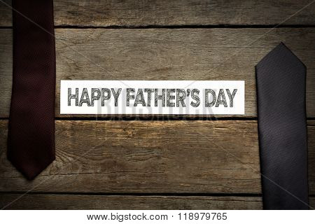Happy Father's Day inscription with ties on wooden background. Greetings and presents
