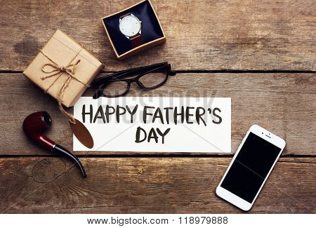 Happy Father's Day inscription with mobile phone and pipe on wooden background. Greetings and presents
