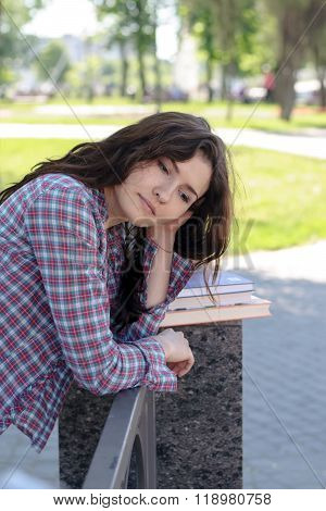 Student grieves over textbooks in the park. Concept: study college exam knowledge.