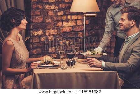 Waiter serving a plate of salad to stylish wealthy couple in a restaurant.