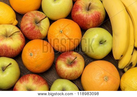 Tasty Fruit Background With Orange, Apples And Banana On The Wooden Boards Table