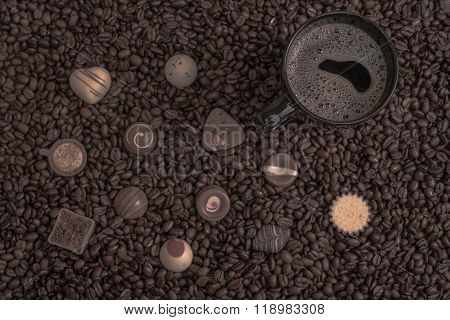 Coffee Beans Background And Black Cup With Pralines