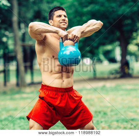 Male athlete exercising with kettlebell