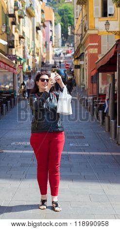 Female Tourist Standing In Town Centre Taking A Photo With Her Smartphone