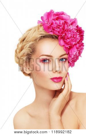 Portrait of young beautiful healthy blonde woman with clean make-up and pink peony flowers in her hair touching her face over white background, copy space