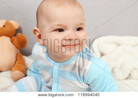 Adorable baby with teddy bears on sofa in the room, close up