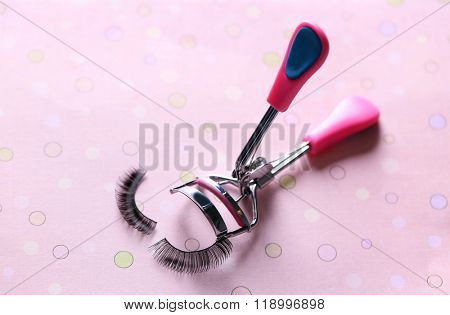 Curler and false eyelashes on a pink background, close up