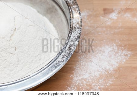 Flour in bowl on wooden table background