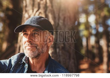Senior Man Sitting In Woods On A Summer Day