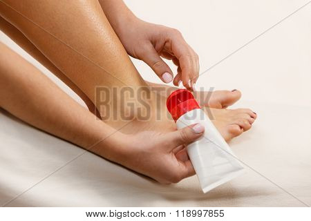 Woman Putting Ointment On Bad Ankle Applying Cream