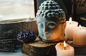 spiritual ritual meditation face of Buddha ametist candles on old wooden background poster