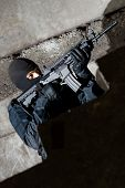 stock photo of extremist  - Armed soldier in black uniform with a rifle - JPG