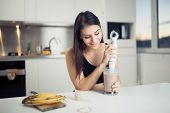 Постер, плакат: Woman with hand blender making sweet banana chocolate protein powder milkshake smoothie
