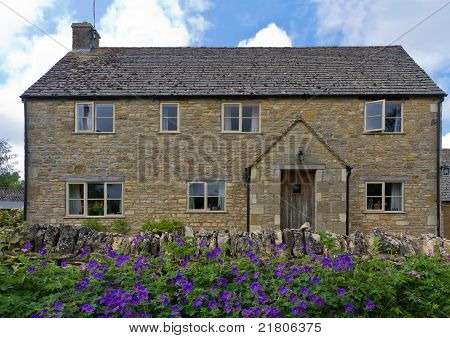 Cottage with flowers in Upper Slaughter, Cotswolds, UK