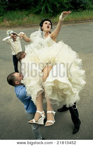 A happy bride tossed into sky by a group of groomsmen