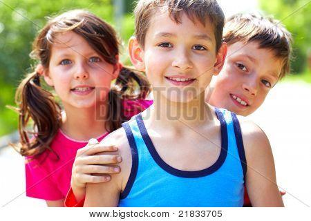 Retrato de tres amiguitos mirando a cámara y sonriendo