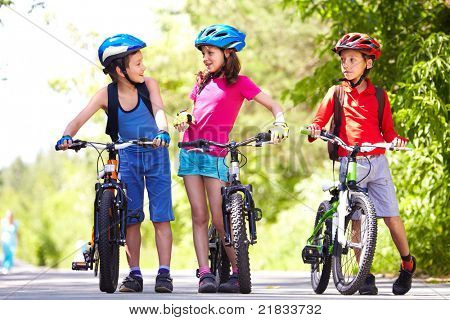 Portrait of three little children with their bikes