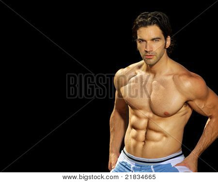 Sexy male fitness model on black background with lots of copy space