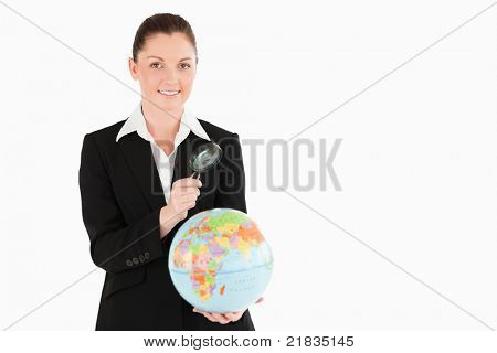 Pretty female in suit holding a globe and using a magnifying glass while standing against a white background