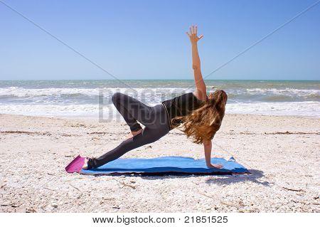 Woman Doing Yoga Exercise On Beach In Vasisthasana Or Side Plank Pose