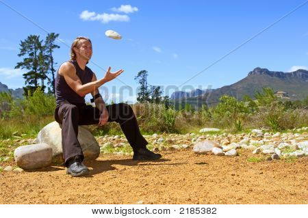 Young Attractive Man Is Tossing A Rock