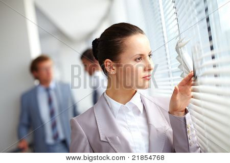Businesswoman looking through window against her colleagues