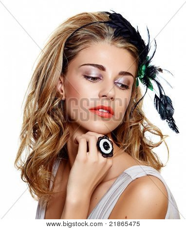 young woman portrait wearing beautiful vintage feather headband on long curly hair and coral fashion lipstick. Model has naturally beautiful skin texture preserved in retouch