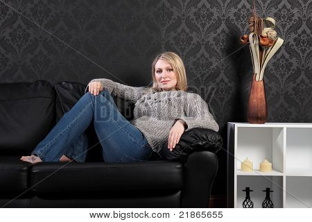 Beautiful Blonde Woman Home On Sofa In Jumper