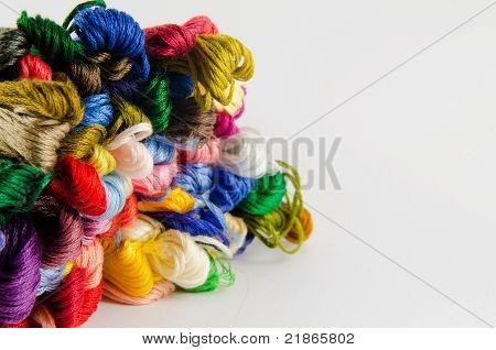 Colorful skeins of thread in a pile over white