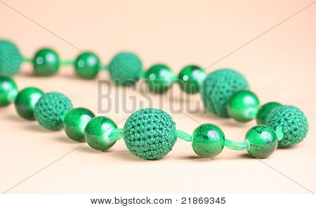 Green Necklace At Pink Background