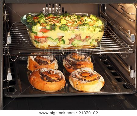 Fresh baked poppy seed rolls and casserole dish with bechamel sauce in oven. Hot air allows the burning of different dishes simultaneously.