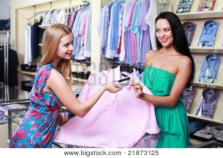 Shopper at a clothing store pays by credit card