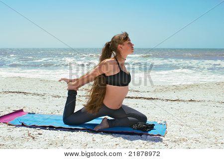 Woman Doing Yoga Exercise On Empty Beach In Kapotasana Or Pigeon Pose