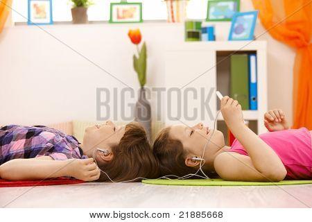 Schulmädchen hören von Musik über Kopfhörer am mp3-Player zusammen, smiling, am Boden liegen.?