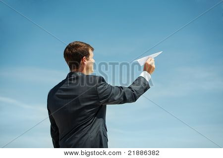 Photo of businessman holding paper aircraft in stretched hand before launching it