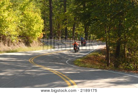 Two Motorcyclists Driving On A Winding Road
